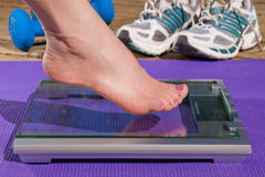 Woman stepping on to a scale. Stock Images