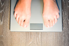Woman stepping on weight scale Stock Images