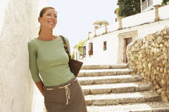 Woman On Steps Leaning On Wall In Granada. Happy middle aged woman on steps leaning on wall in Granada; Spain Royalty Free Stock Photos