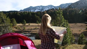 Woman steps out of tent, checks map at sunrise stock video footage