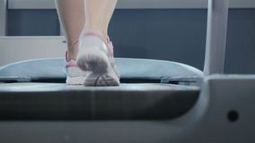 Woman steps on the treadmill. Close-up. The camera moves from the right to the left. Young woman wearing sporty sneakers is in the gym. Sporty young woman is at stock footage