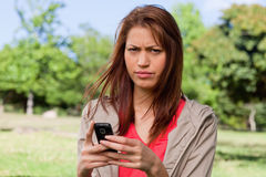 Woman with a stern expression on her face while holding a phone Stock Photography