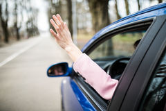Woman sticking arm out of the car window on roadtrip. Female driver hand feeling the air and freedom. Woman sticking arm out of the car window on roadtrip royalty free stock photography