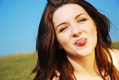 Woman sticking her tongue out. A beautiful young woman sticking her tongue out on a field with a blue sky stock photography