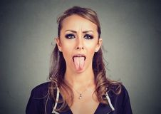 Closeup portrait of a woman sticking her tongue out Stock Photo