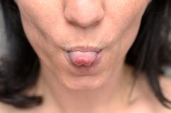 Woman sticking out her tongue at the camera. In a close up cropped view of her mouth conceptual of rudeness or playfulness Royalty Free Stock Photos