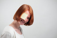 Woman with Sticky Note. A smiling woman peeking behind a sticky note placed over her eye Royalty Free Stock Photography