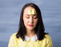 Woman with sticky note on her forehead Royalty Free Stock Photography