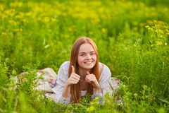 Woman stiiting on the green grass. And showing thumbs up Royalty Free Stock Photo