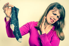 Woman with stinky sock of her husband - retro style. Woman with stinky sock of her husband - unpleasant smell concept - retro style stock photography