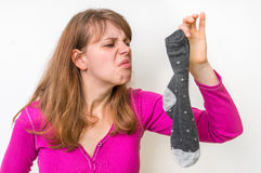 Woman with stinky sock of her husband Stock Image