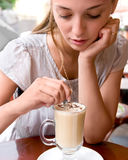 Woman is stirring coffee. Portrait of beautiful charming woman is stirring coffee in outdoor cafe and thinking Royalty Free Stock Photos