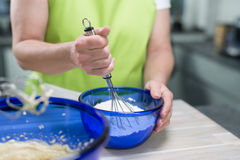 Woman is stirring dough with a eggbeater in a blueish bowl in he Royalty Free Stock Photography