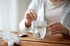 Woman stirring medication in cup with spoon Royalty Free Stock Photography