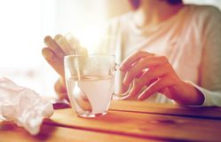 Woman stirring medication in cup with spoon Royalty Free Stock Images