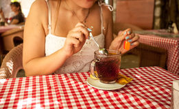 Woman stirring sugar in tea at cafe Stock Photography