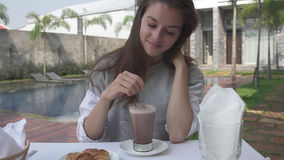 Woman stirs cacao during morning breakfast near pool on luxury villa. Beautiful young woman stirs cacao during morning breakfast near pool on luxury villa royalty free stock photos