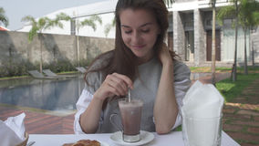 Woman stirs cacao during morning breakfast near pool on luxury villa. Beautiful young woman stirs cacao during morning breakfast near pool on luxury villa stock photo