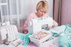 Woman stitch at home on sewing machine. Young woman stitch at home on sewing machine stock photography