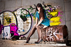 Woman in stockings sitting on barrel against wall with graffiti Royalty Free Stock Photos