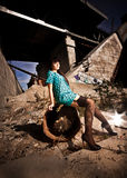 Woman in stockings sitting on rusty barrel at scrapyard Stock Photo