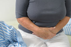 Woman with stomach ache clutching her stomach Royalty Free Stock Photography