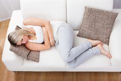 Woman with stomach ache. Portrait of woman with stomach ache sitting sofa Stock Images
