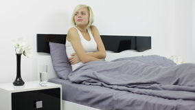Woman stomach pain, sick girl lying on bed, hold stock video