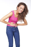 Woman with stomach pains. Young woman with stomach pains in studio with white background Royalty Free Stock Image