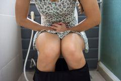 Woman stomachache or menstruation in restroom. Closeup Asian woman sit on toilet in bathroom and hold her painful stomach of bad stomachache with copy space for Stock Photography