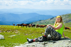 Woman  on stone against herd of horses Royalty Free Stock Photography