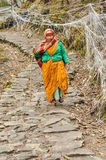 Woman on stony road in Nepal. Pathivara Devi, Nepal - circa May 2012: Native woman with headcloth walks down stony road with help of wooden stick in Pathivara Stock Photography