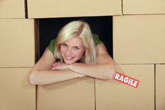 Woman stood amongst cardboard boxes Stock Image