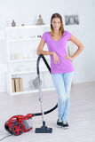 Woman stood with red vacuum cleaner. Woman stood with a red vacuum cleaner Stock Photo
