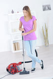 Woman stood with vacuum cleaner Stock Photography