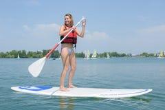 Woman stood on windsurfing board holding oar. Woman stood on windsurfing board holding an oar stock photography
