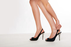 Woman stooping to adjust her shoe. Cropped view image of a beautiful shapely pair of female legs wearing high heels with the woman stooping to adjust her shoe Royalty Free Stock Image