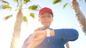 Woman stops while jogging to check the data in the smart watch application, rests and continues to run. Smartwatch concept. Woman using smart watch. Woman stops stock video