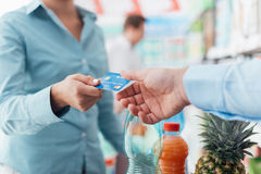Woman at the store checkout. Woman at the supermarket checkout, she is giving her credit card to the cashier, retail and payments concept Royalty Free Stock Images