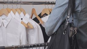 A woman in a store chooses clothes and steals her discreetly, putting them in a bag