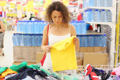 Woman in store holding shirt and looking on it Royalty Free Stock Photo