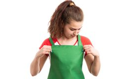 Woman storekeeper or retail worker adjusting her apron. Young woman storekeeper or retail worker adjusting her green apron as employee getting ready for work stock photo