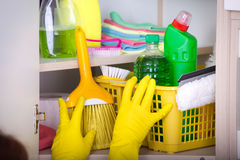 Woman storing cleaning tools in pantry Royalty Free Stock Photography