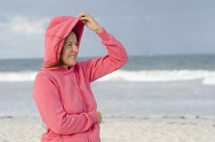 Woman in stormy weather at the beach Stock Photo