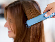 Woman straightening hair Royalty Free Stock Photography