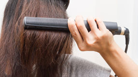 Woman straightening hair. Royalty Free Stock Images