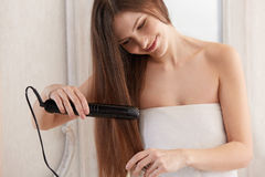 Woman straightening hair with straightener Royalty Free Stock Images