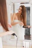 Woman straightening hair with straightener Stock Image