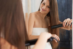 Woman straightening hair with straightener Stock Photo