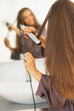Woman straightening hair with straightener Royalty Free Stock Photo